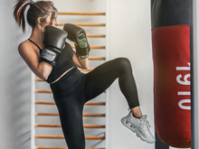 Girl About To Throw A Kick. She Is In Attack Position And In Profile. She Is Wearing A Ponytail And Her Hair Up. She Is Practicing Kick Boxing.
