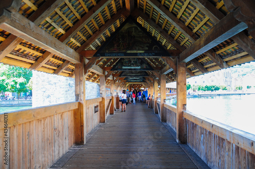 Photo People walking in chapel bridge, in Lucerne, Switzerland.