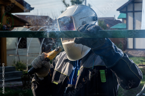 Fototapeta Close up of the a welder welds a fence on the construction site in the village