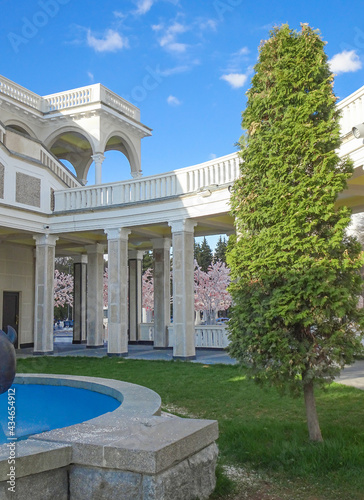 Foto Outside galleries, balconies and colonnades against the sky and flowering trees,