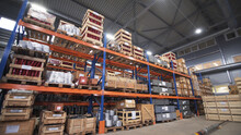 Warehouse With Racks And Shelves, Filled With Wooden Boxes On Pallets. Distribution Products. Logistics Business. Interior Large Warehouse With Freight Stacked High. Written Marking On Boxes
