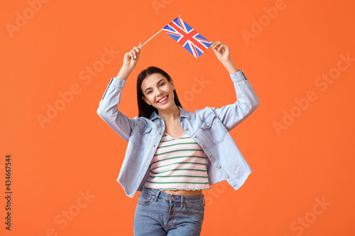 Obraz na plátne Beautiful young woman with the flag of Great Britain on color background