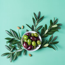 Fresh Olives And Olive Tree Branch On A Table