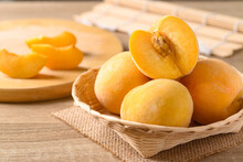 Yellow Peaches In A Bamboo Basket On Wooden Table