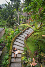 Woman Carrying Breakfast Tray Down Curved Stair Case Surrounded By Lush Forest To A Bungalow In Bali.