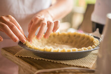 Woman Pressing The Edges Of A Pie Crust In A Pan.