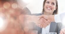 Composition Of Businessman Handshake Over Smiling Businesswoman And Orange Spots Of Light