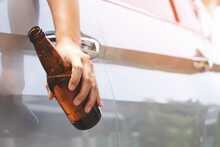 Close Up Hand Drunk Young Woman Holding Beer Bottle While Driving A Car. Don't Drink And Drive Concept.