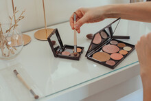 Close-up Of A Woman's Hand Dipping A Make-up Brush In A Make-up Palette On A Dressing Table