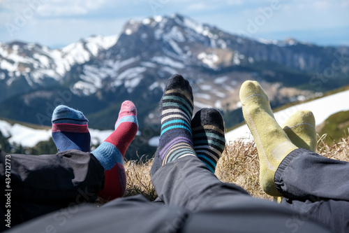 Detail photo with hikers feet and their colored socks relaxing on a mountain peak