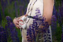 Close-up Of A Pregnant Woman Standing Amongst Flowers Holding Baby Booties Against Her Belly
