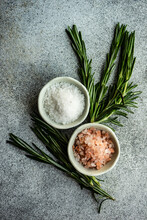 Overhead View Of Pink Himalayan Salt And Rock Salt On A Table With Fresh Rosemary Sprigs