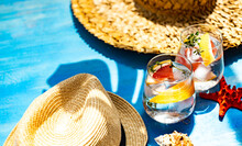 Two Glasses Of Ice Water With Grapefruit And Thyme With Straw Hats, Sea Shell And Starfish Ornaments