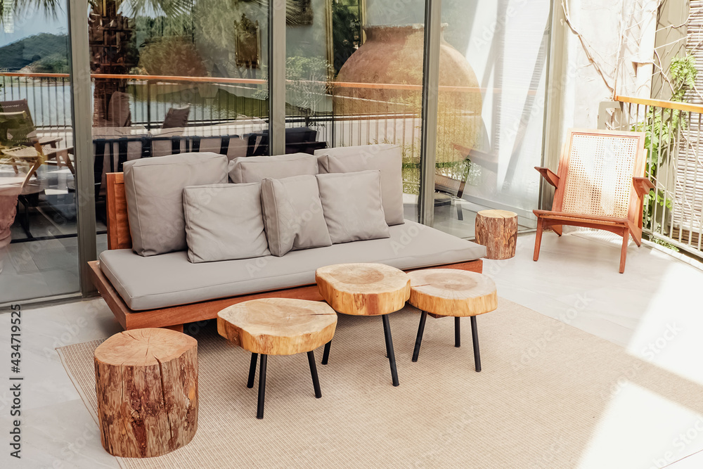 Wooden sofa and coffee tables on stylish modern terrace
