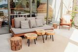 Fototapeta Kawa jest smaczna - Wooden sofa and coffee tables on stylish modern terrace