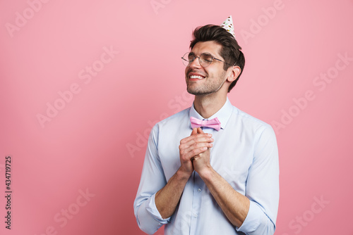Fototapeta Young white man wearing bow tie and party cone smiling and gesturing