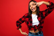 Young Happy Positive Sexy Attractive Brunette Woman With Sincere Emotions Wearing White T-shirt And Hipster Red Check Shirt Isolated Over Red Background With Empty Space