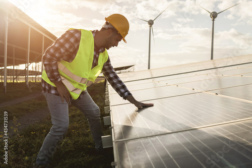 Fototapeta Young man working at renewable energy farm - Eco and environment concept - Focus
