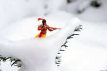 Small Plastic Toy American Indian In The Snow Outdoors