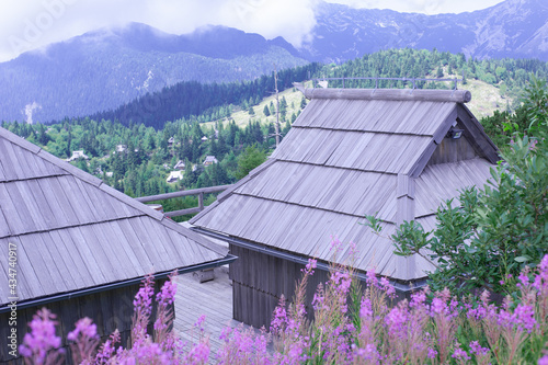 wooden roofs of authentic slovenian mountain huts in a green alpine valley for s Fototapet