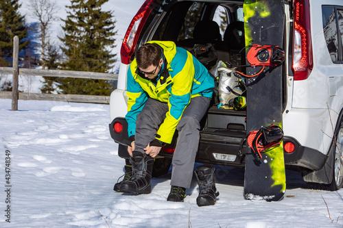 Carta da parati man sitting in car trunk changing for snowboard