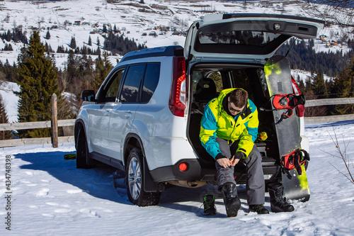 Fotografia man sitting in car trunk changing for snowboard