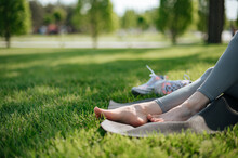 The Girl Sit On Yoga Mat Outdoor. Feet On A Background Of Green Grass