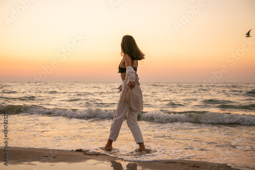 Tableau sur Toile A slender girl in white clothes runs along the beach against the background of the sea