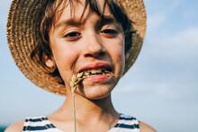 Portrait Of Boy Wearing Hat Biting Crop Against Sky