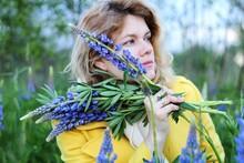 Portrait Of Beautiful Woman Holding Purple Flowering Plant