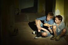 Sad Boys Sitting On Floor  In A Dark Cellar