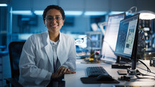 Beautiful Black Latin Woman Wearing Glasses Smiling Charmingly Looking At Camera. Young Intelligent Female Scientist Working In Laboratory. Technological Laboratory In Bokeh Blue As Background