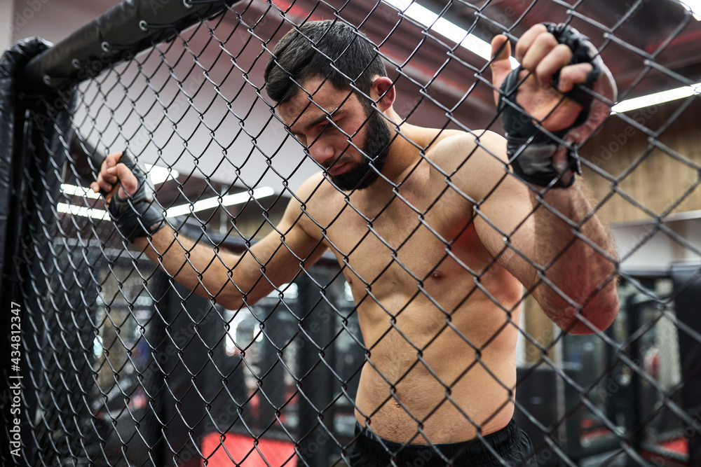 Mixed Martial Arts. mma, strong fighter in the octagon, resting in ring after fight, need some rest, shirtless muscular male is looking down