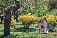 Happy Woman Walking With Daughter In Blooming Spring Garden By Yellow Flowering Bush. Family Relaxes Outdoors