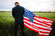 4th Of July. Independence Day. A Man With The American Flag In His Hands Against The Background Of A Green Wheat Field. Freedom Concept. Young Man In A Plaid Shirt With A Flag.