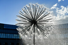 A Round Spherical Fountain That Spews Water Under Pressure. The Globular Structure Is Similar To A Dandelion. Water Bris. Windows Of A Modern Building In The Background.