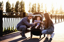 Stylish Family Walk In The Park By The River With A Stroller And Little Daughter. Parents Take Care Of Their Sweet Child. Little Girl Having Fun And Smiling While Playing With Parents