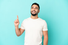 Young Arab Man Isolated On Blue Background Pointing Up And Surprised