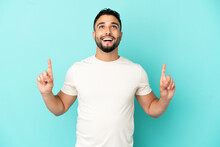 Young Arab Man Isolated On Blue Background Surprised And Pointing Up