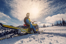Snowmobile Female Rider Riding On Beautiful Mountain Slope