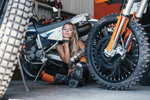 Female Wearing  Motorcycle Clothes And Underwear Resting In Garage With Enduro Motorcycles