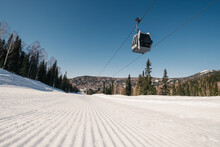 Gondola Lift In The Ski Resort On Steep Slope Groomed And Prepared For Skiing