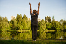 Adult Woman Doing Exercises By The Lake In The Park On A Summer Day