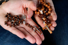 Catholic Man And Woman Praying Together At Home. Close Up On Hands With Prayer Beads.   France.