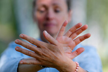 Woman Practicing Qi Gong Or Tai Chi Exercise   In Nature. Close Up On Hands.