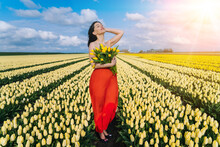 Beautiful Woman In Summer Dres Standing In Colorful Tulip Flower Fields In Amsterdam Region, Holland, Netherlands. Magical Netherlands Landscape With Tulip Field In Holland Trevel And Spring Concept.