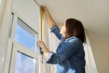 Service For Sewing And Hanging Curtains. Woman With Tape Measure Measuring Window