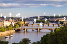 Map Pin Icons On Prague Cityscape. Scenic View Of Buildings And Bridges Over Vltava River In Prague, Czech Republic, On A Sunny Day.