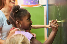 African Girl Paints With Chalk On The Blackboard