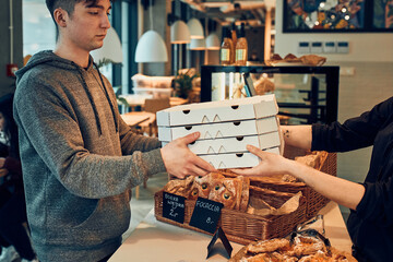 Young man receiving fresh pizza in boxes takeaway from female worker in a pizzeria and coffee shop. Man collecting his order from the pizzeria during coronavirus lockdown